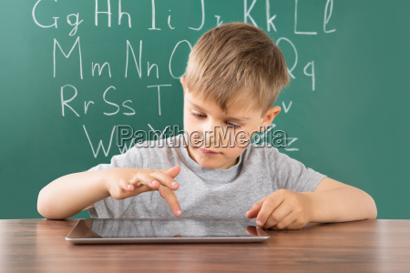 boy using digital tablet at school