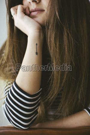 ung kvinde med pil tatovering pa
