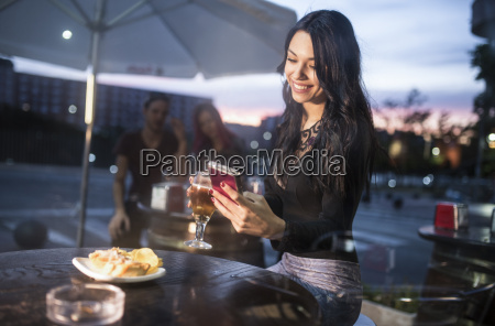 young woman sitting in bar using