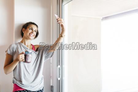 smilende ung kvinde med sund drik