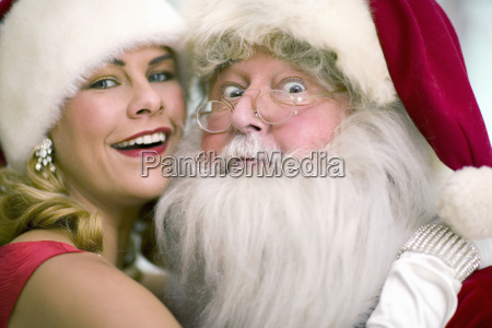 woman wearing santa claus hat hugging