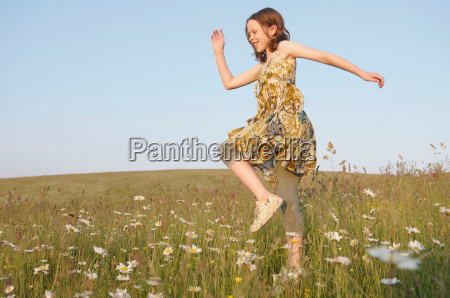 young girl skips in meadow