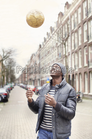 young man on street throwing soccer