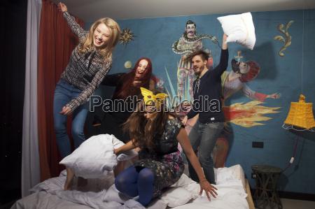 four adult friends having pillow fight