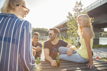 four young friends drinking beer on