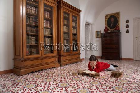 girl lying on floor reading books