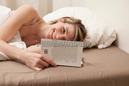 young woman reading in bed