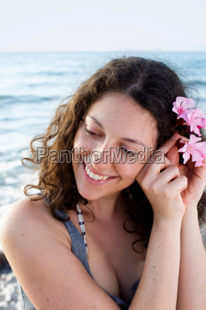 smiling woman putting flower in her
