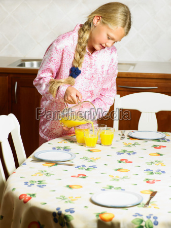young girl pouring orange juice