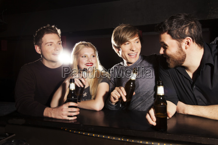 four friends drinking bottled beer in