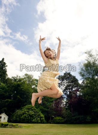 girl jumping in garden