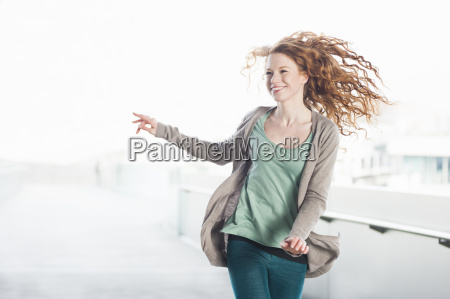 excited young woman running on rooftop