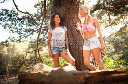 two female friends leaning against tree