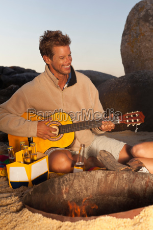 man playing guitar with beer on