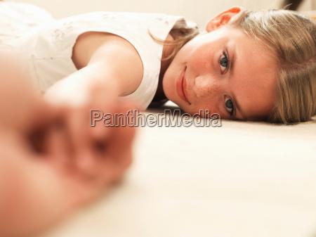 girl smiling resting head on floor