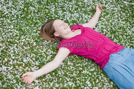 young girl lying in grass