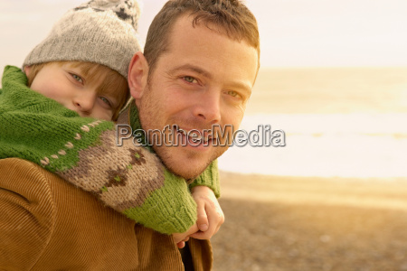 man carrying young boy on beach