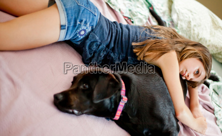 girl relaxing with dog on bed