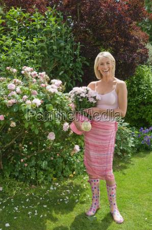 woman standing in rose garden