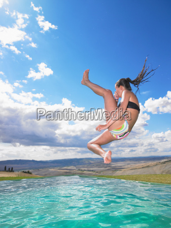 woman jumping in swimming pool