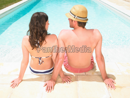 couple sitting by pool