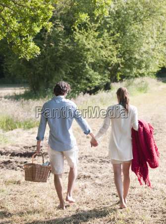 couple walking in field with picnic