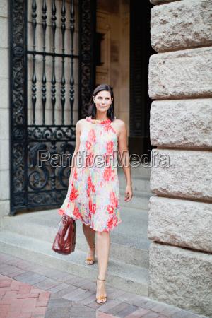 smilende kvinde gar pa byens gade