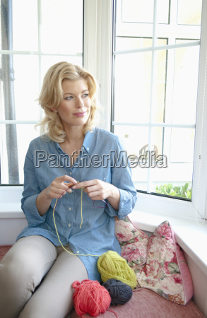 portrait of mid adult woman knitting