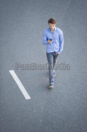 mid adult man walking along road