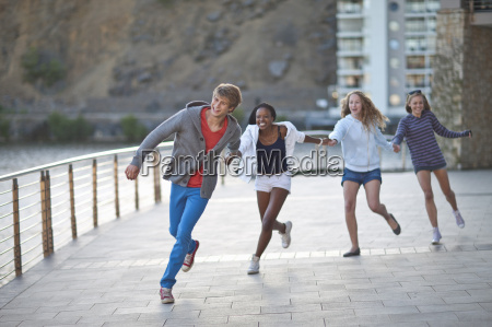 four young adult friends running and