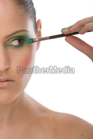 woman applying eye makeup up with