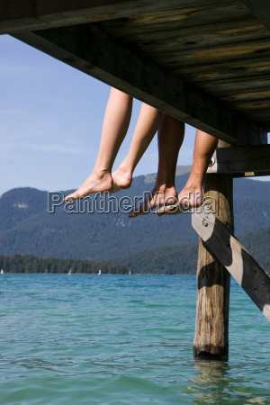 two people sitting barefoot by a