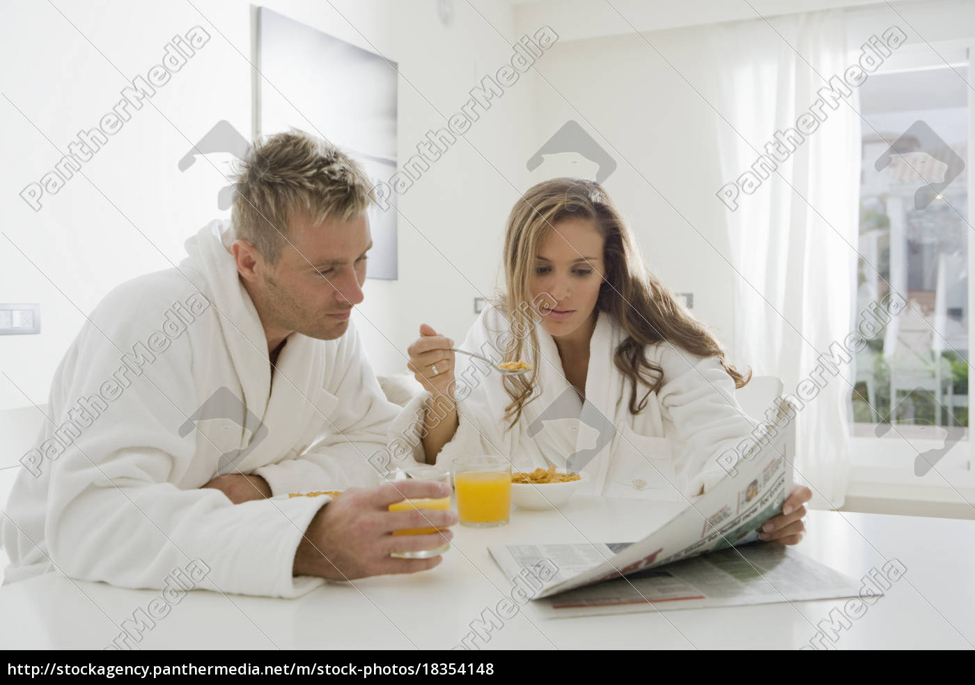 young, couple, reading, paper, at, breakfast - 18354148
