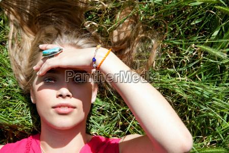 teenage girl lying in tall grass