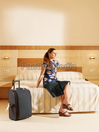 woman sitting on hotel bed by
