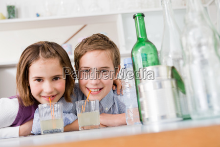 boy and girl drinking lemonade smiling