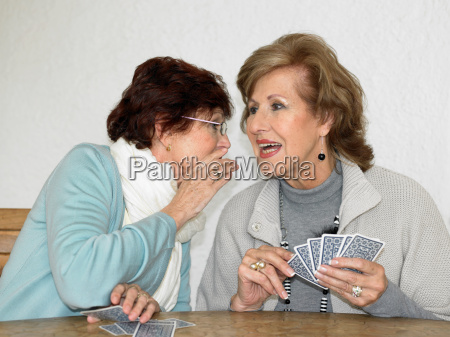 two senior adult women playing cards