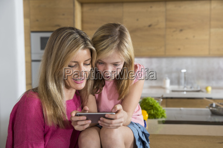 mid adult woman and daughter reading