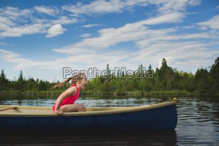 excited girl sitting in canoe on