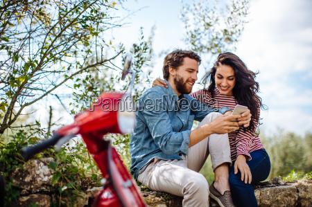 ungt par sidder pa vaeggen i