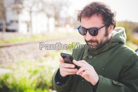 mid adult man texting on smartphone