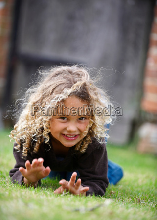 young girl crawls on grass toward
