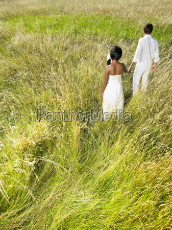 married couple walking in a field