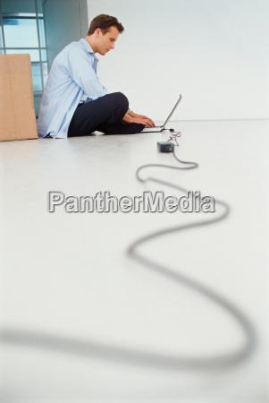 businessman using laptop on floor