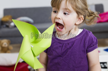girl excited over paper windmill at