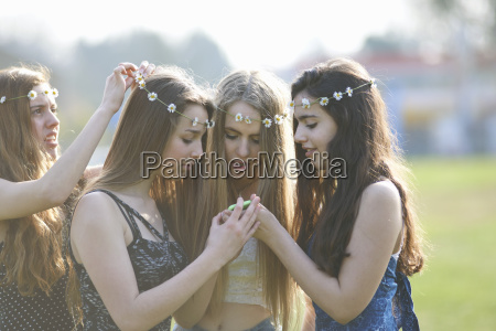 four teenage girls wearing daisy chain
