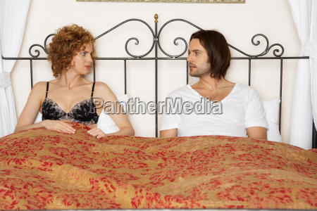 young couple sitting in bed
