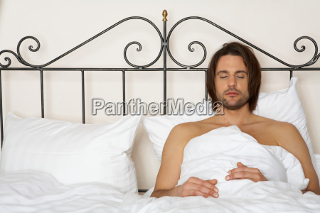 young man lying in bed eyes