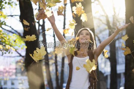 mid voksen kvinde smide efterarsblade i