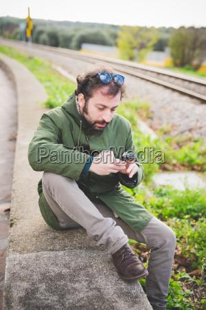 mid adult man sitting on wall